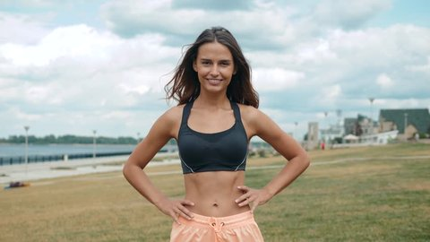 Mid section portrait happy smiling of fit woman's torso with her hands on hips. Female runner outdoors slim skinny belly stomatch muscles abdominal.