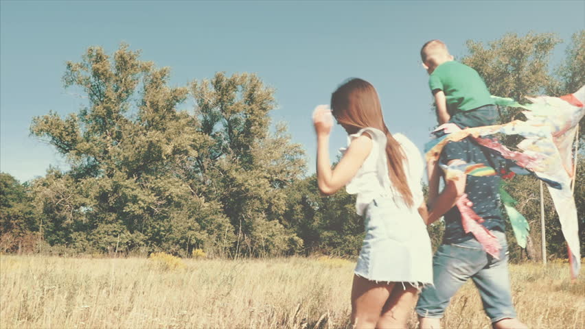 Happy family, mom, dad and son are walking in nature, launching a kite.  #1013551292