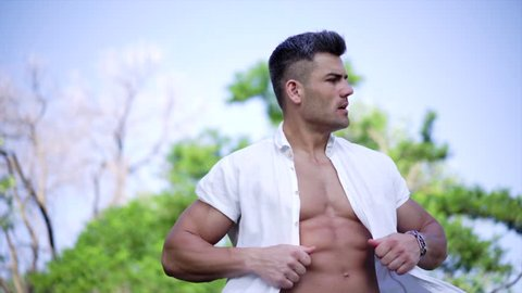 Young fit man opening shirt on naked muscular torso. Flushed man feeling hot in on a summer's day. Young traveller wandering in the city park.