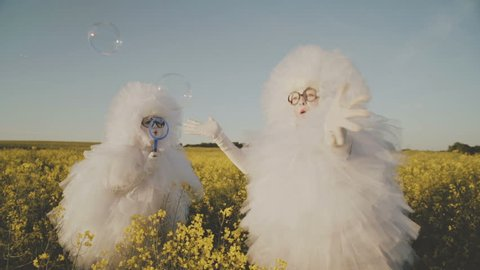 Two cheerful clowns mime in white suits snowflakes blow bubbles in the field. HD