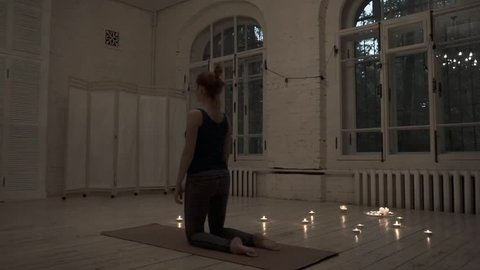 Back bends side view. Yoga instructor demonstrates tibetian set of exercises. Burning candles behind