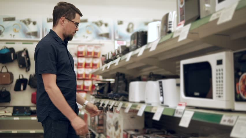 Man is watching on a rack with electric toaster and taking one of them in hands. He is reading labels and looking on a costs in a sales area | Shutterstock HD Video #1013587022