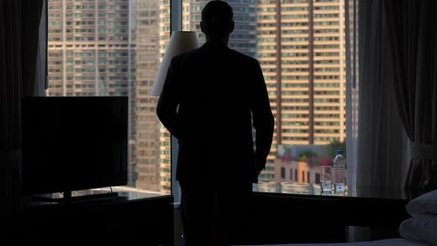 Business man stay with hands akimbo, silhouette against room window. Man wear black jacket, put arms on hips and look out to city, Then turn around and walk away