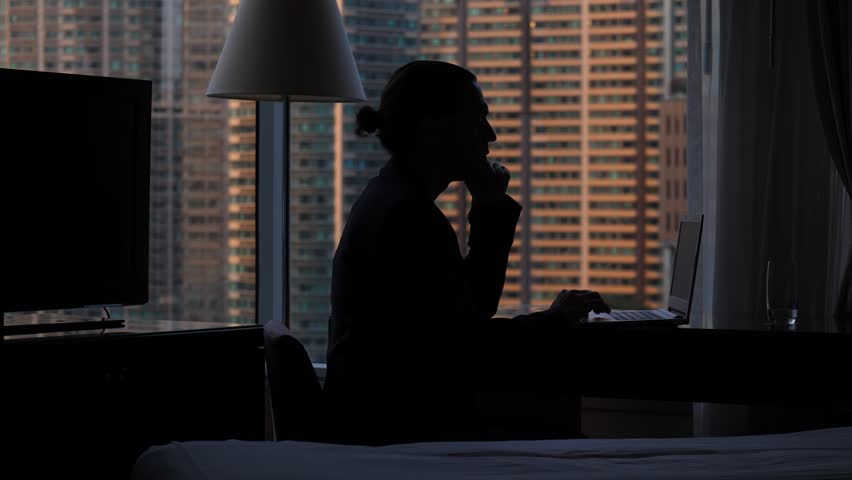 Man finish work, close laptop and look out window, black silhouette of person sitting by desk against window. Apartment building seen blurred outdoors, dark room interior   Shutterstock HD Video #1013597402