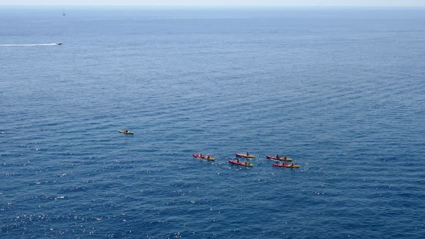 Long shot aerial footage of a group of sea kayakers following their leader in the open sea with a motorboat in background
