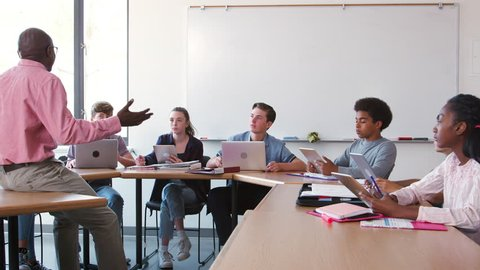 High School Teacher Talking To Pupils Using Digital Devices In Technology Class