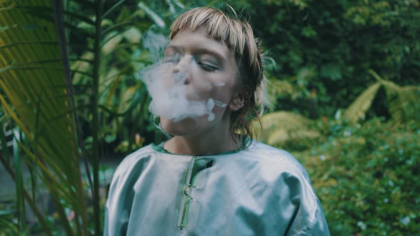 Beautiful fashion girl posing with e-cigarette and smoke puffing out over tropical rain forest jungle. Portrait of stylish hipster female outdoor | Shutterstock HD Video #1013600492