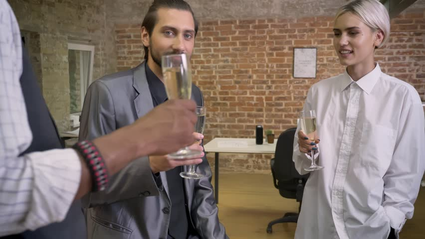 Three multy-ethnic workers are sitting in office, clink glasses, drinking champagne, communication concept | Shutterstock HD Video #1013617082