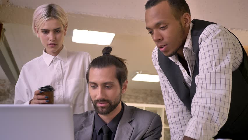 Three multy-ethnic workers discuss idea on laptop in office, coworking concept, communication concept | Shutterstock HD Video #1013617112
