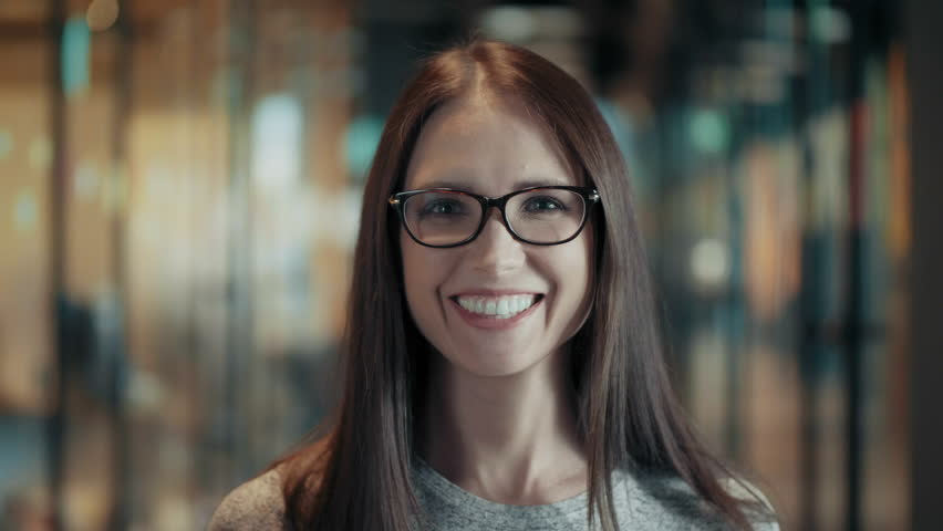 Portrait of attractive smiling young woman in glasses close up face of happy brunette female with long hair in good mood casual team leader or businesswoman in modern start up office positive emotions | Shutterstock HD Video #1013618162