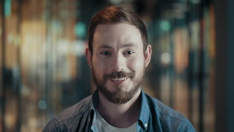 Portrait of creative young male with beard and mustache close up face of european cheerful guy in modern big start up office casual man in good positive mood looks and smiles