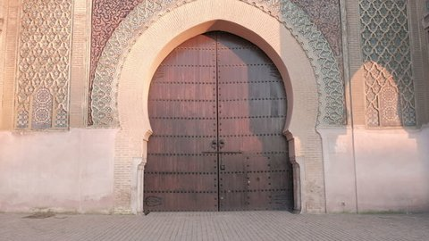 Camera tilt down view from top to bottom of Bab Mansour Gate wooden door in Meknes, Morocco late afternoon