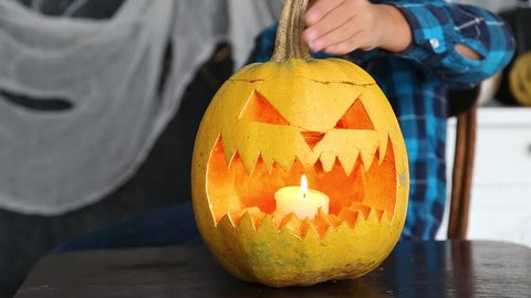 Young boy cutting scary face in pumpkin for Halloween celebration. Closeup view of freshly cutted evil face and burning candle inside of vegetable ready for party.