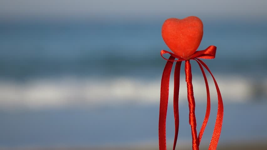 Valentine's day greeting card concept, red heart on pristine sandy beach, honeymoon vacation background.