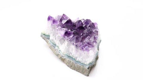 Footage of amazing Violet Crystal Stone macro mineral. Purple rough amethyst quartz crystals on white rotating platform (30 fps)