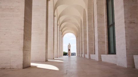Young woman walks through a squared colonnade in Rome