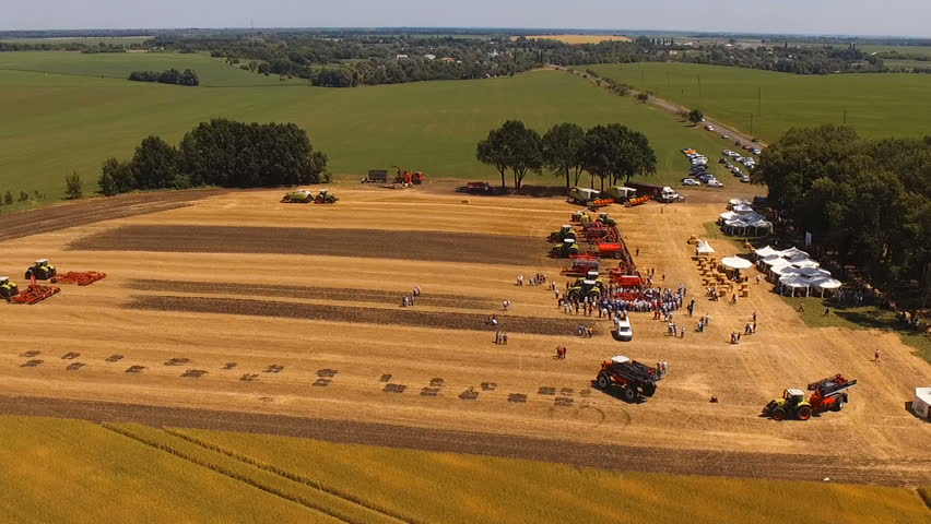 Aerial footage. Exhibition of modern agricultural machinery. Flight over the field with combines, tractors, seeders, sprayers, harrows