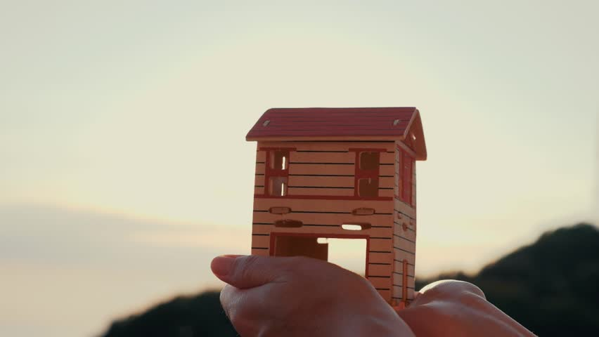 Silhouette of a paper house in hands at sunset in the sun. | Shutterstock HD Video #1013679032