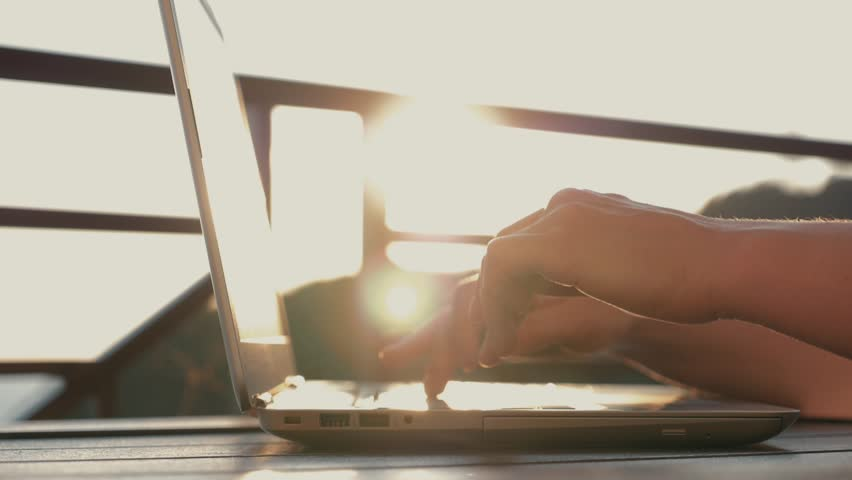 A woman typing text on a laptop at her workplace. Girl at sunset in the sun. Electronic Online Shopping   Shutterstock HD Video #1013679152
