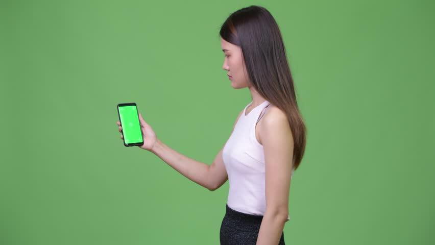 Young beautiful Asian businesswoman showing phone | Shutterstock HD Video #1013692352