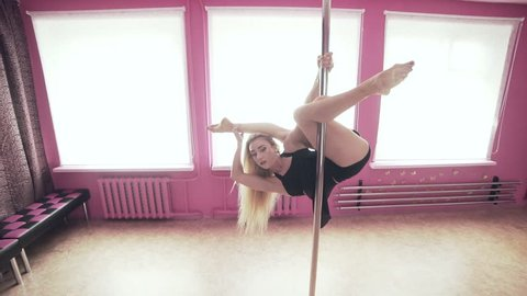 Female poledance woman splitting her legs while hanging on pole. Beautiful woman doing pole dance. Fitness and sport concept in slow motion