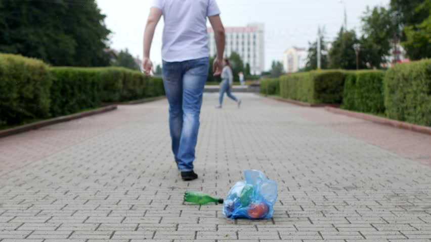 A young man throws out a package of garbage in the center of the city, litterbug | Shutterstock HD Video #1013726432