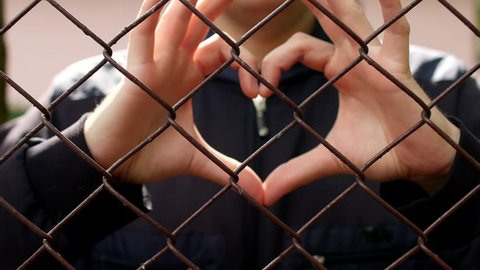 A man through the grid lattice shows a gesture of the heart, close-up, prohibition of same-sex marriages, LGBT