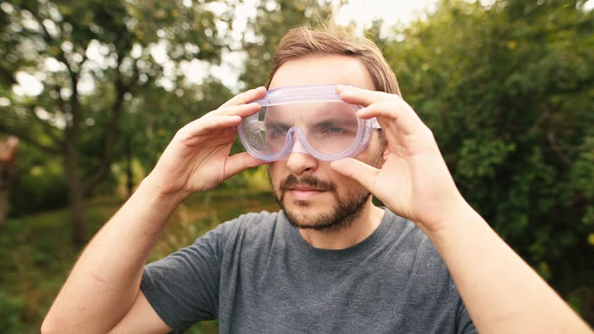 Young bearded lawn mower wearing transparent glasses protection and and isolating headphones. Lawn care concept. | Shutterstock HD Video #1013743922