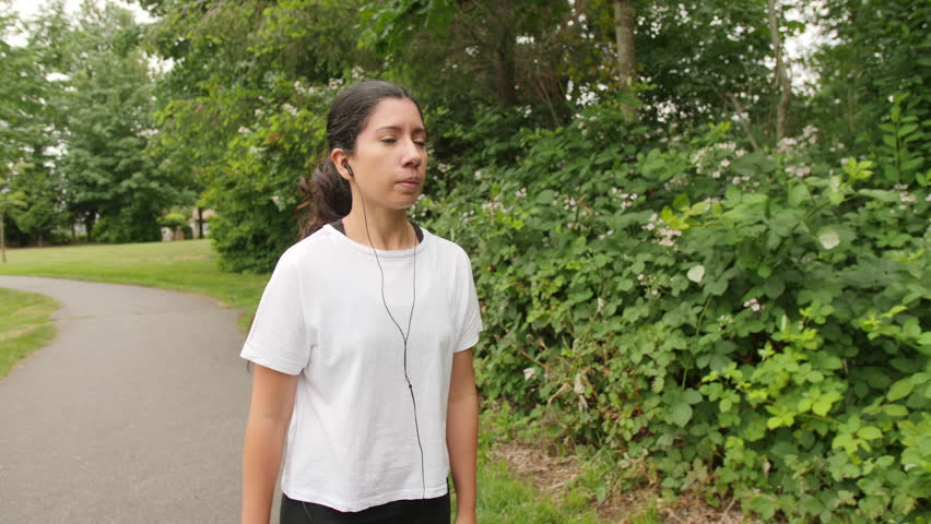 Upper Body Shot of Latina Woman Walking in Lush Green Park Wearing White Shirt and Headphones with Hair in Ponytail | Shutterstock HD Video #1013755712