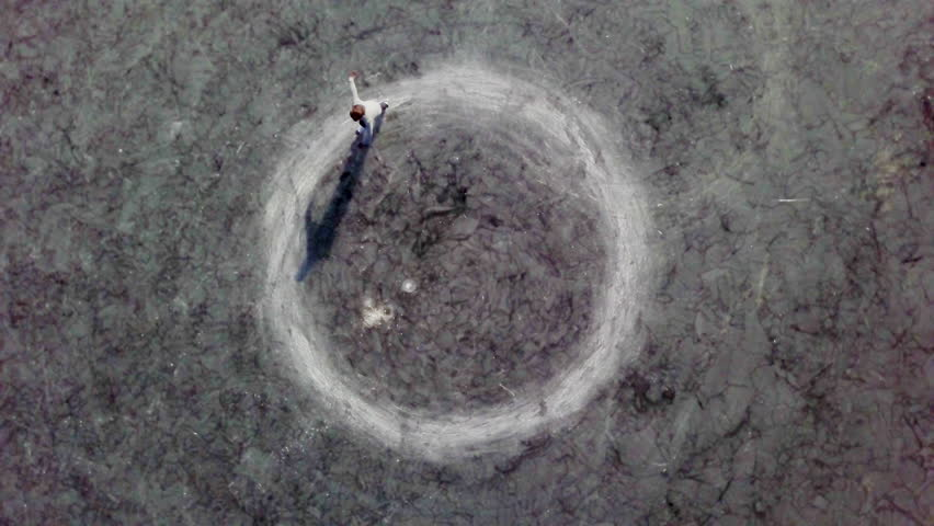 Bird's-eye view of an ice-skater on a frozen lake doing circles. Camera rotating counter clockwise, following the skater. #1013766392