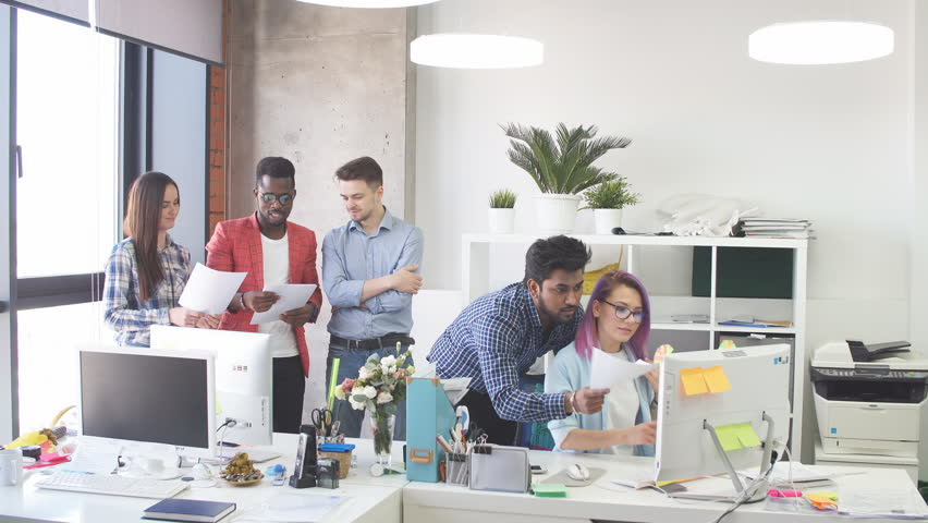 Startup business multiethnic team discussing new business plan in modern bright office interior brainstorming, working on laptop and tablet computer | Shutterstock HD Video #1013799992