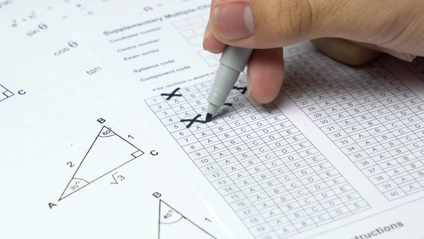Asian student hand doing fill square box examination by random guessing answer in mathematics subject.