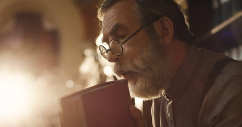 Close up of the old gray haired man in glasses blowing a dust from a book in the library before reading it.