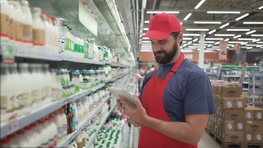 Handsome male merchandiser checking milk products with digital tablet | Shutterstock HD Video #1013816432