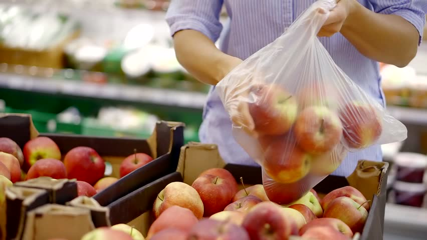 Woman is choosing apples from a box in a supermarket and putting in a plastic bag and fastening | Shutterstock HD Video #1013819102