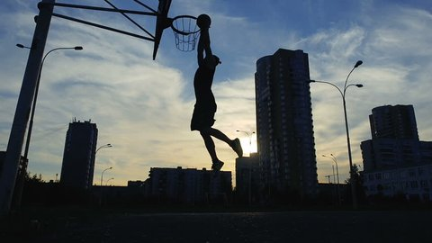 Man Basketball Player Training Playing Basketball Field. Basketball Player Bouncing the Ball. Slow motion shot of basketball player training.