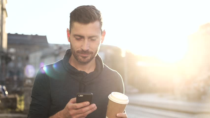 Happily Smiling Attractive Man Walking down the Street. Typing on his Smartphone with Interest. Enjoying the Evening Walk. Drinking Delicious Coffe. Crowded City on the Background.