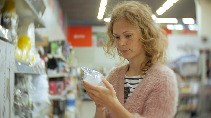 Young woman stands near the supermarket shelf and selects the products 4k | Shutterstock HD Video #1013883872