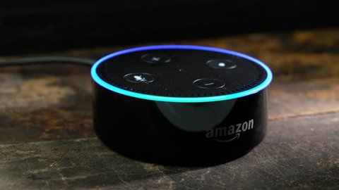 TOKYO, JAPAN - JULY 16TH, 2018. Amazon's Echo Dot, Alexa virtual assistant on wooden background.