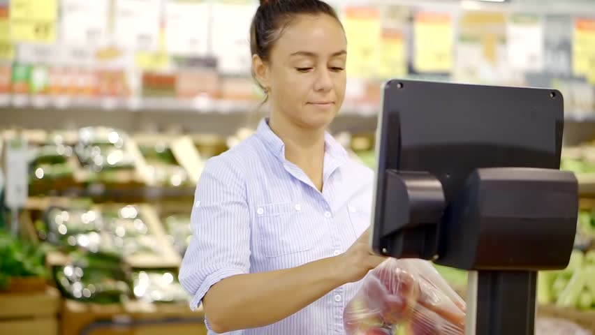 Beautiful brunette woman puts a bag of fresh apples on a digital scale in a supermarket. | Shutterstock HD Video #1013886482