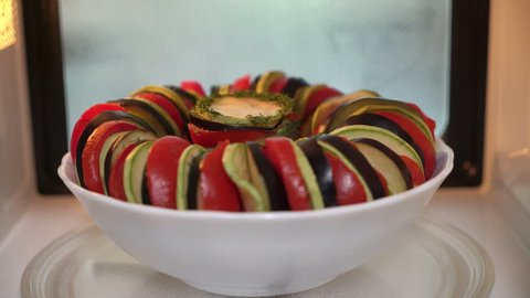 Using microwave for cooking vegetables. Making ratatouille in microwave.