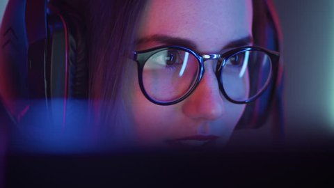Beautiful Friendly Pro Gamer Girl Does Video Game Gameplaystream, Wearing Glasses. Attractive Geek Girl with Cool Neon Retro Colors in Background. Shot on RED EPIC-W 8K Helium Cinema Camera.