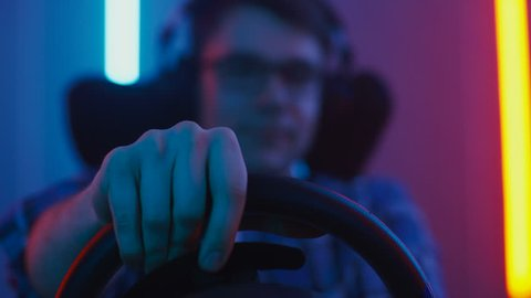 Portrait of the Pro Gamer Sitting in the Racing Seat Simulator Cockpit with Steering Wheel and Playing in Car Racing Online Video Game. Shot on RED EPIC-W 8K Helium Cinema Camera.