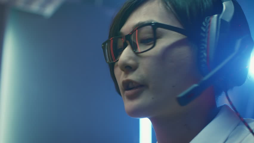 Close-up Portrait of the Professional Gamer Playing in Online Video Game, He's wearing Glasses, talks/ chats with His Teammates / Friends through Headphones. Shot on RED EPIC-W 8K Helium Cinema Camera