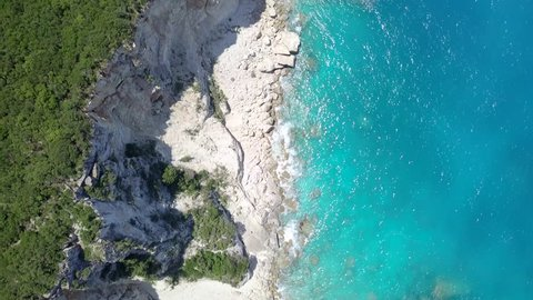 4k aerial top down view moving forward over mediterranean coastline cliff edge with white sand and turquoise sea