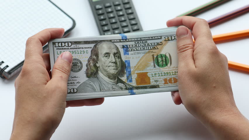 Counting money on the working desk with stationary, pack of dollars   Shutterstock HD Video #1013923682