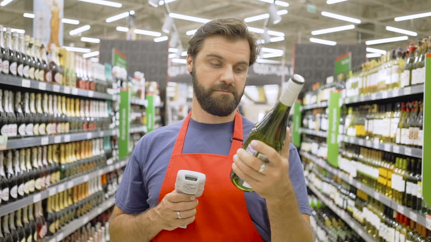 Supermarket employee in red aport scanning bottle barcode at wine section in supermarket | Shutterstock HD Video #1013929292