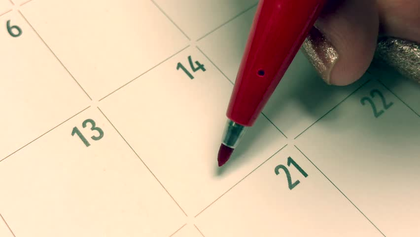 Writing RED HEART on 14th February on calendar with a red marker. The concept of Valentine's day