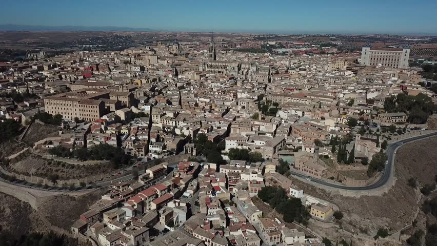 Aerial view of an ancient Spanish city Toledo in Castilla la Mancha. Drone flying over the historic center where we can see Alcazar, Cathedral, the city walls and bridges