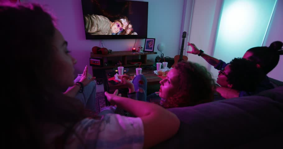 Multi-ethnic teenage friends chilling at home, watching film on TV and eating fast food